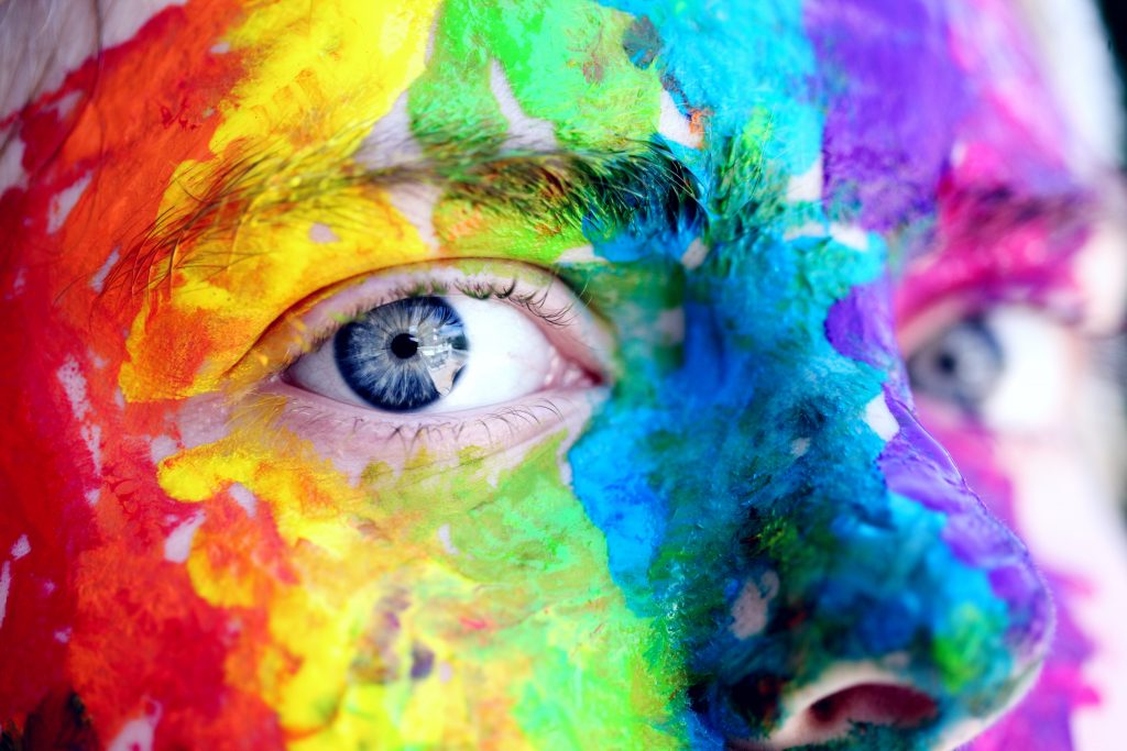 Close up of blue eyes with rainbow paint on face synonymous with LGBTQ movement